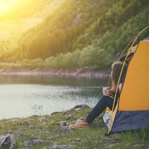 Packliste Camping: Checkliste zum Ausdrucken: Frau sitzt im Zelt und guckt heraus in die Landschaft