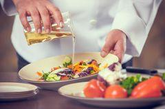 Ernährung bei Arthrose: Koch kippt Öl über Salat