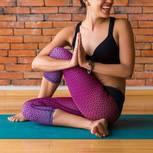 Yoga oder Pilates: Frau sitzt auf einer Yogamatte