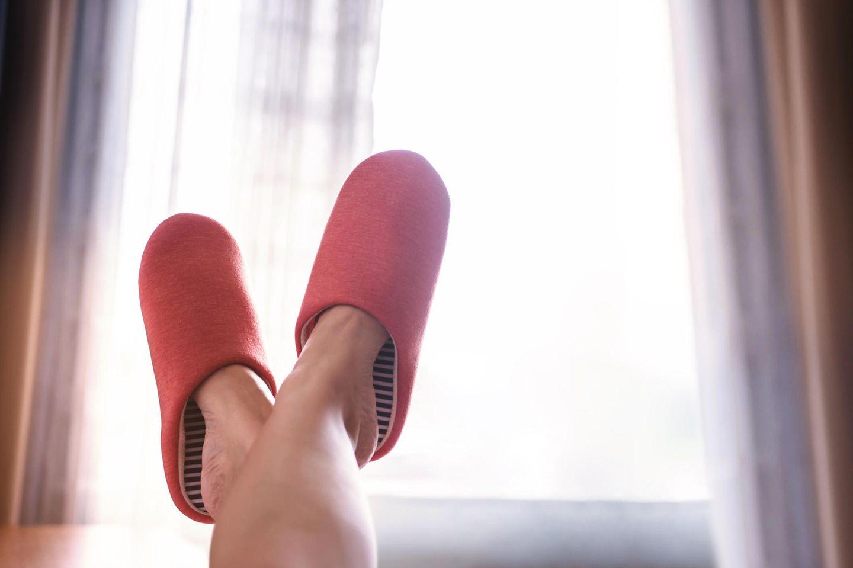 Gewohnheiten ändern: Gekreuzte Frauenbeine mit roten Filzpantoffeln