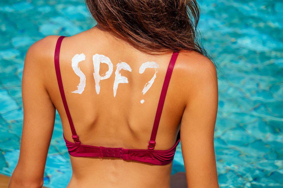Sonnenschutzfaktor: Frau mit Bikini und Sonnencreme auf dem Rücken im Pool