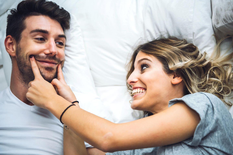 Parship-Umfrage: Eine Frau schiebt die Mundwinkel ihres Partners nach oben