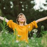Das gewisse Etwas: Eine glückliche blonde Frau in gelbem Pulli auf einer Wiese