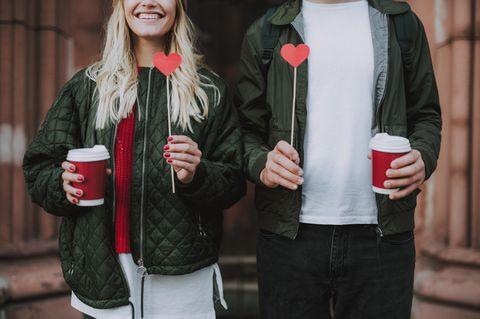 Welcher Dating-Typ bist du? Ein Mann und eine Frau mit Herzen am Stock