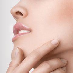 Nasenhaare entfernen: Frauengesicht bei dem Nasen- und Mundbereich sowie eine Hand zu sehen ist