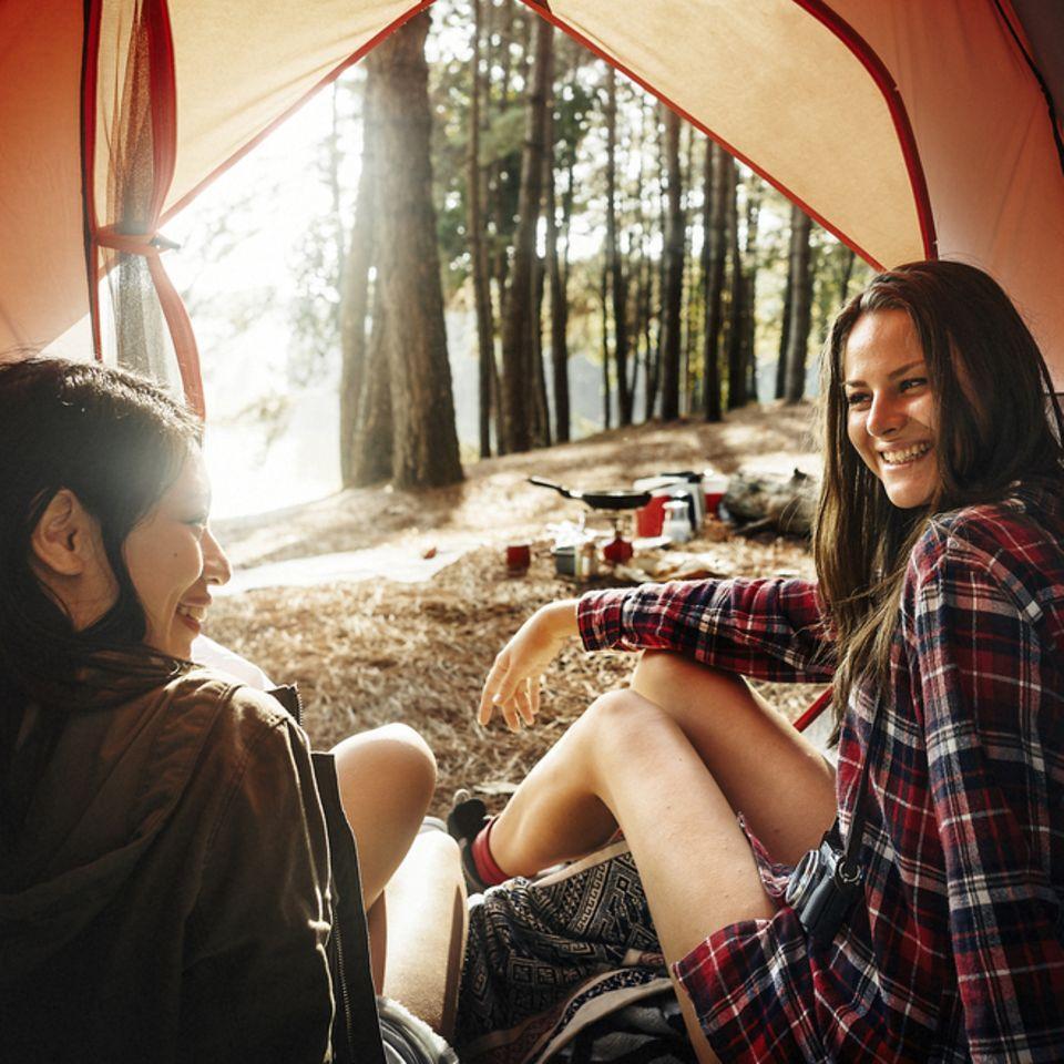 Camping Tipps für einen gelungenen Urlaub: Zwei Frauen sitzen im offenen Zelt und lachen
