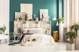 Wandgestaltung Schlafzimmer: 6 kreative Ideen: Bett vor einer kleinen Bücherwand und grüner Wandfarbe