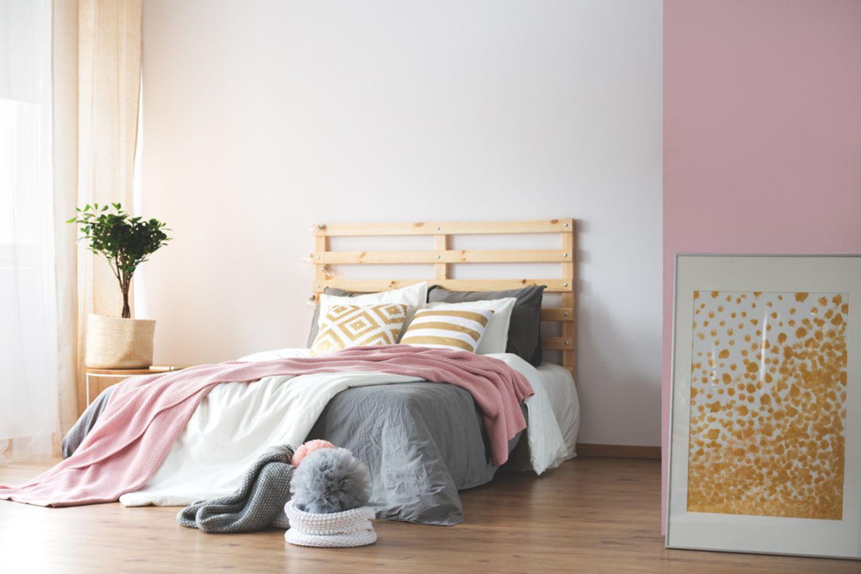 Wandgestaltung Schlafzimmer: 6 kreative Ideen: Bett mit rosa Decke und rechts einer rosafarbenen Wand