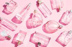 Parfum selber machen: Ganz viele Parfumflakons vor rosafarbenem Hintergrund