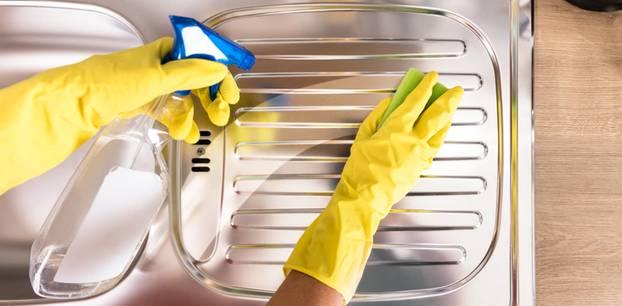 Edelstahl reinigen: 4 effektive Hausmittel. Spüle wird besprüht und sauber gewischt