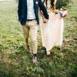 Brautpaar läuft Händchen haltend über Wiese