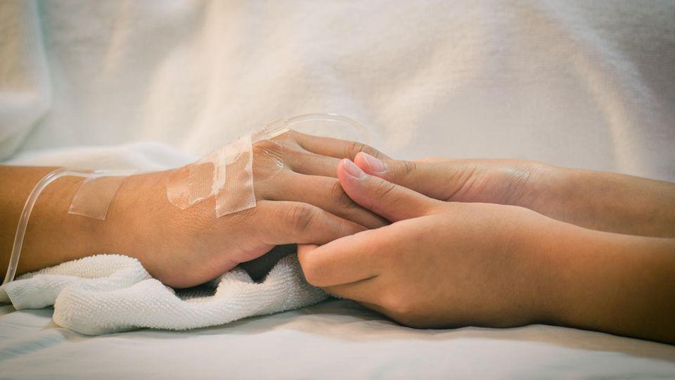 Mutter erwacht nach 27 Jahren aus dem Koma: Hände auf Krankenhausbett