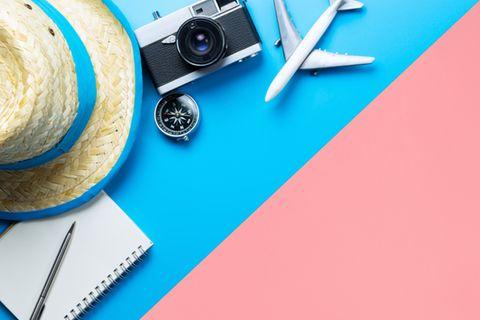 Langstreckenflug: 10 Tipps für einen entspannten Flug: Kamera, Kompass und Modellflugzeug liegen auf bunter Fläche