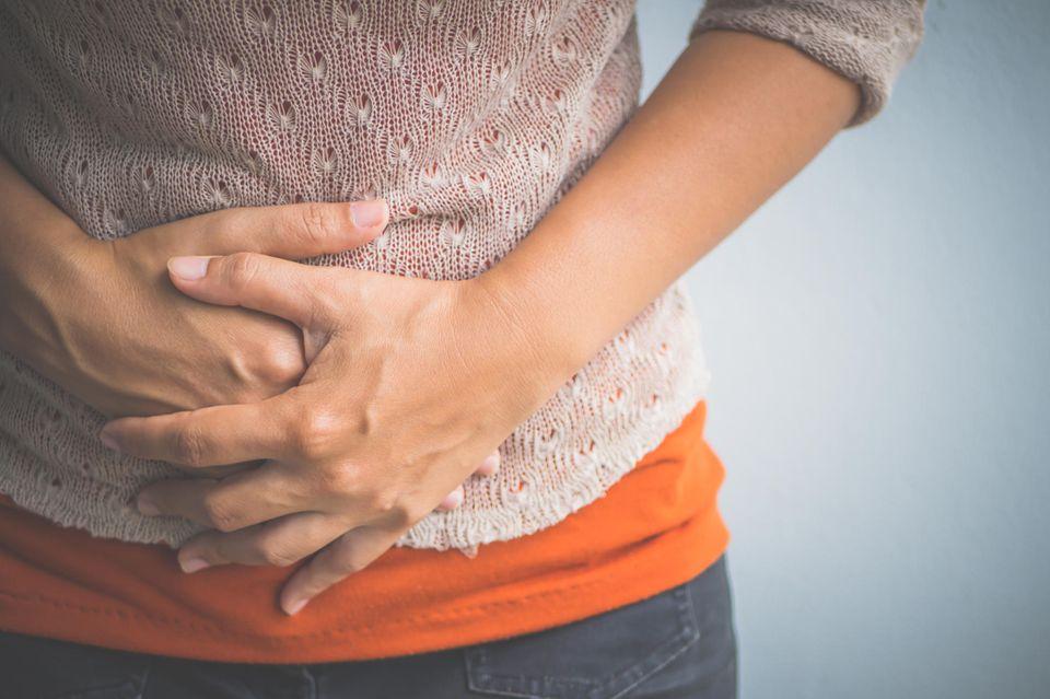 Leben ohne Gallenblase: Frau hält sich den Magen