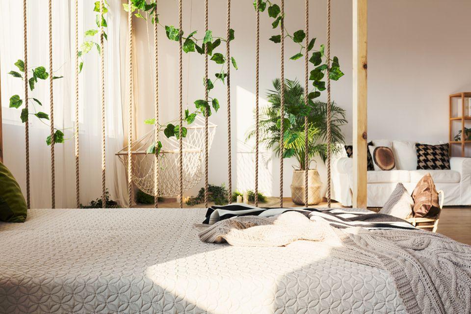 Raumteiler Ideen: 9 kreative Lösungen: Bett mit einem Raumteiler aus Seilen und Pflanzen, dahinter Sofa und Hängematte