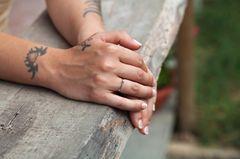 Tattoo am Handgelenk: Frau mit Tattoos am Handgelenk
