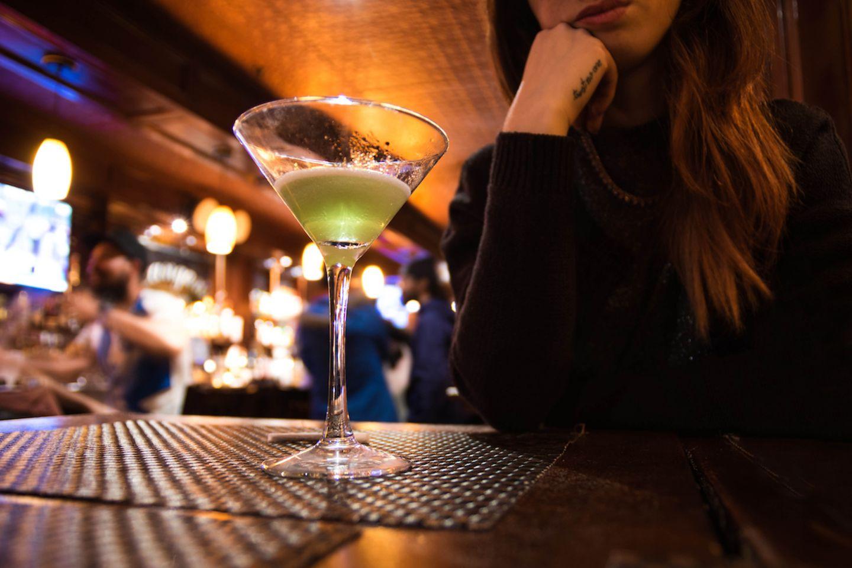 Was sind schlechte Dates? Frau sitzt in Bar vor ihrem Cocktail Glas
