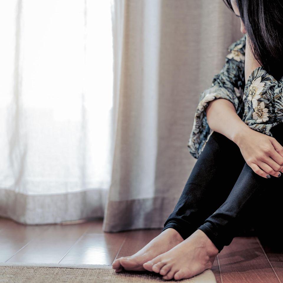 Psychisch krank: Frau sitzt deprimiert auf dem Boden