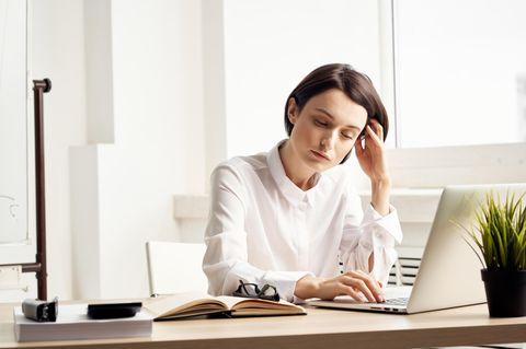 Müde Augen: Frau am Schreibtisch sieht müde aus