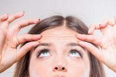Falten auf der Stirn: Frau massiert Falten auf der Stirn weg