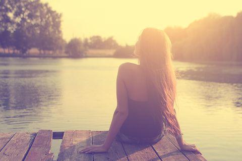 Sonnenstich-Anzeichen: Frau sitzt am Bootssteg in der Sonne