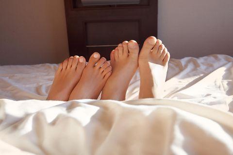 Gründe für keinen Sex in der Beziehung: Zwei Fußpaare nebeneinander liegender Menschen im Bett
