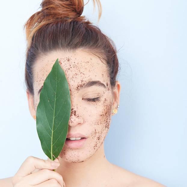 Peeling ohne Mikroplastik: Frau mit Peeling im Gesicht hält grünes Blatt vor das rechte  Auge