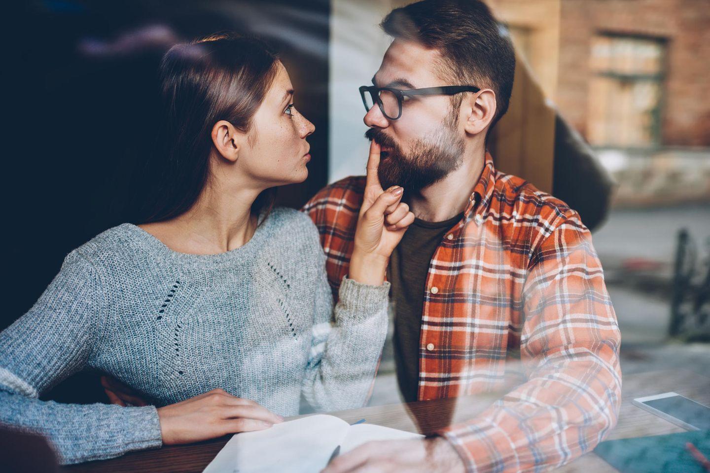 Was sollte man nicht beim Streiten tun? Eine Frau hält ihrem Freund den Finger auf den Mund