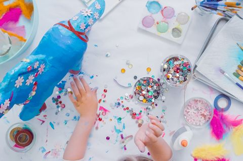 Pappmache Ideen für Kinder und Erwachsene: Kind bemalt Einhorn aus Pappmache