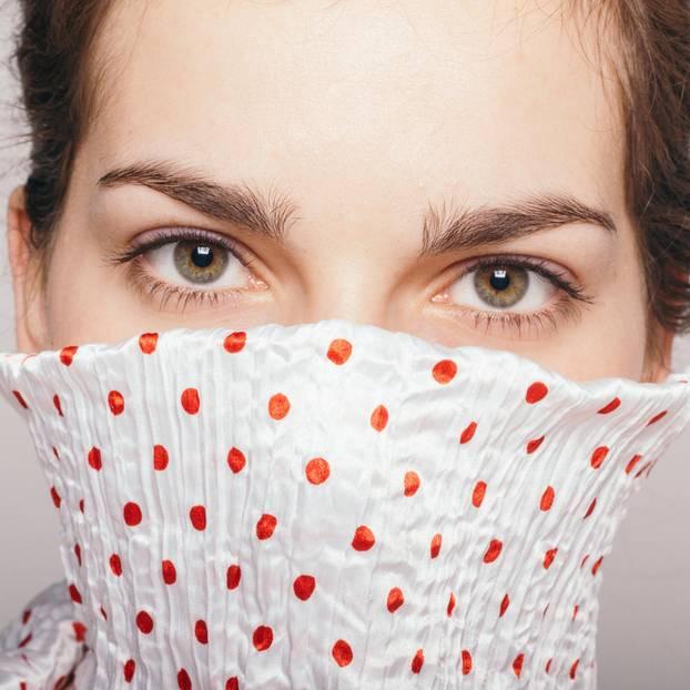 Welche Probleme hat man als introvertierter Mensch? Eine Frau versteckt ihr Gesicht mit dem Kragen ihrer Bluse