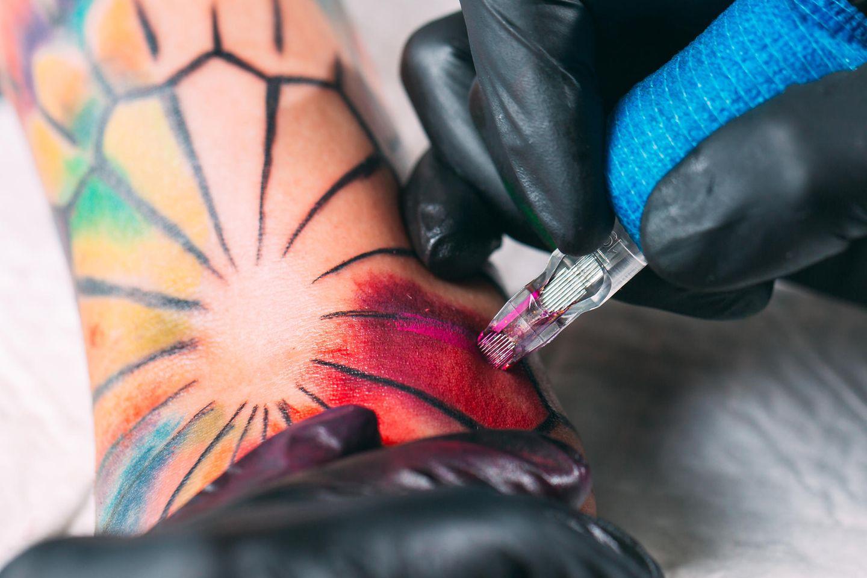 Watercolor Tattoo: Tättowierer sticht das Tattoo