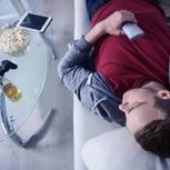 Midlife-Crisis Mann: Ein unmotivierter Mann mit Bier und Popcorn auf dem Sofa