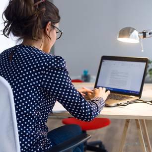 Abschiedsmail an Kollegen: Beispiele und Tipps: Frau sitzt am Schreibtisch mit Laptop und tippt
