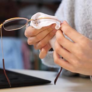 Brille putzen: Frau putzt Brille mit Mikrofasertuch