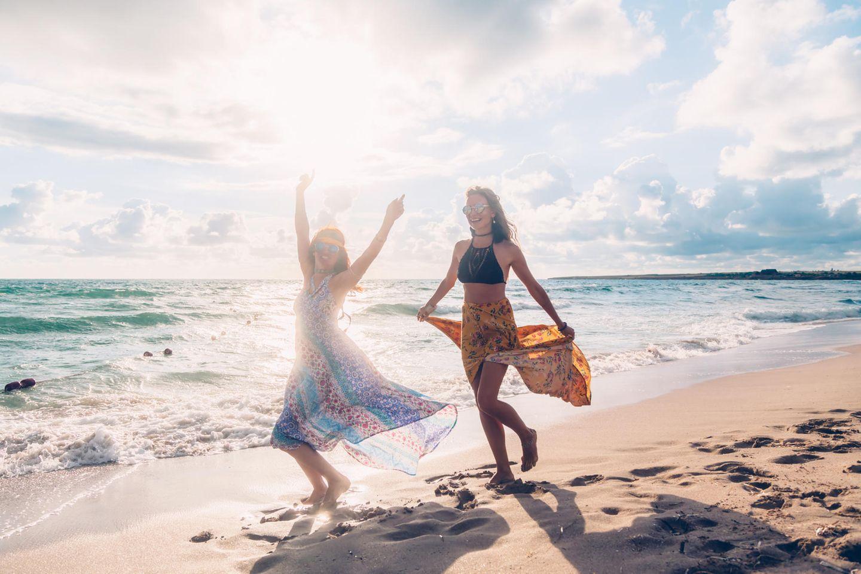 Was sind die Stärken des Löwen? Zwei fröhliche Frauen am Strand