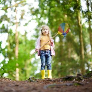 Kindererziehung: Mädchen mit Windrad im Wald