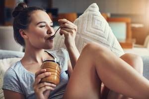 Erdnussbutter: Frau löffelt Erdnussbutter aus Glas