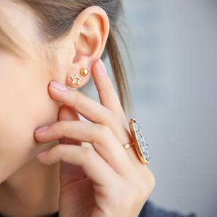 High Lobe: Frau mit Ohrringen und großem Ring am Finger