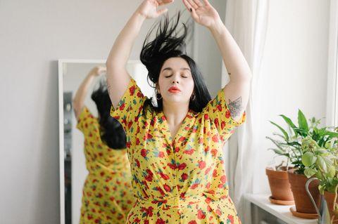 Curvy-Frauen: Frau vorm Spiegel reißt Arme hoch