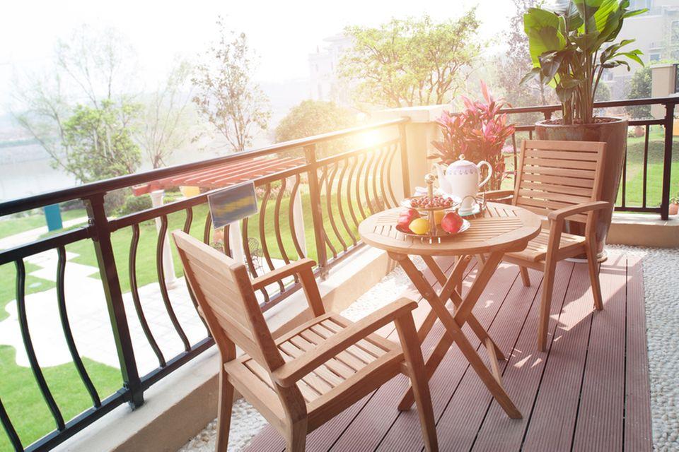Balkonbelag: 5 Böden für einen schönen Balkon: Balkon mit Holzboden-Optik, darauf Tisch und Stühle
