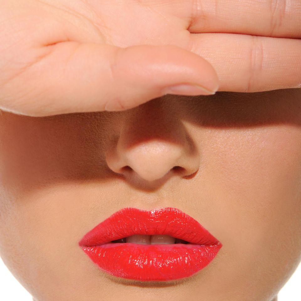 Augenringe abdecken: Frau mit roten Lippen hält sich die Hand vor die Augen
