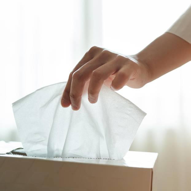 Allergie oder Erkältung: Frau greift nach Taschentuch