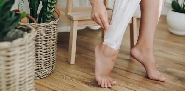 Enthaarungscreme: Frau enthaart sich die Beine mit einer Enthaarungscreme