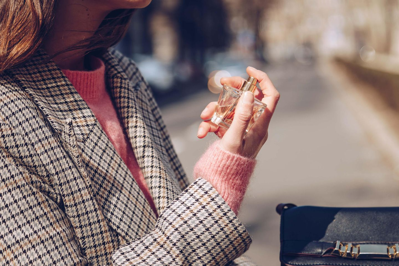 Duftlayering: Frau sprüht sich Parfum auf