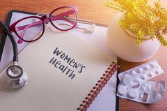 Milchsäurekur - dann ist sie sinnvoll: Notizbuch mit den Worten Women's Health auf einem Tisch mit Tabletten