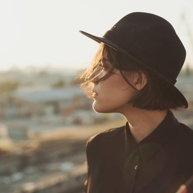 Warum ist man unglücklich? Eine nachdenkliche, unglücklich aussehende Frau mit schwarzem Hut