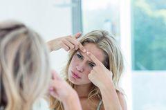 Unterirdische Pickel: Frau steht vor dem Spiegel und drückt Pickel auf der Stirn aus