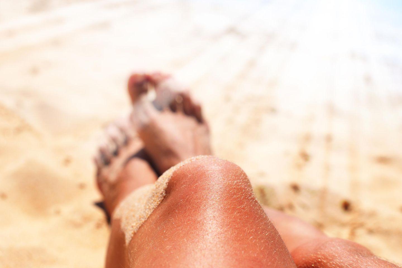 Hitzschlag-Symptome: Stark gebräunte Beine im Sand