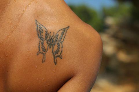 Schmetterling Tattoo: Frau mit Schmetterling Tattoo am Rücken