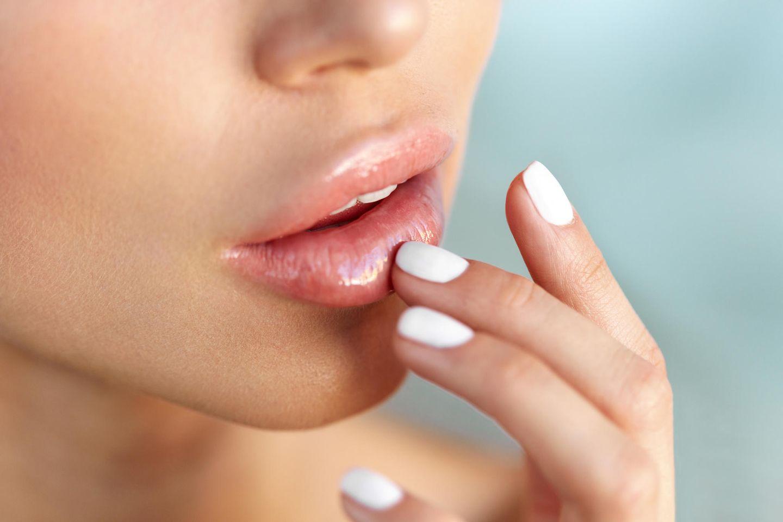 Frau mit Lipgloss und weißem Nagellack